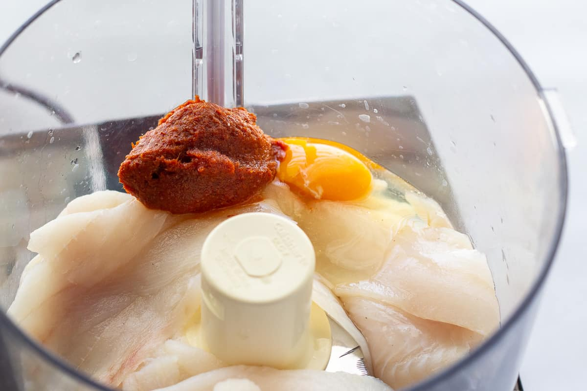 Tilapia, red curry paste, and an egg inside a food processor.