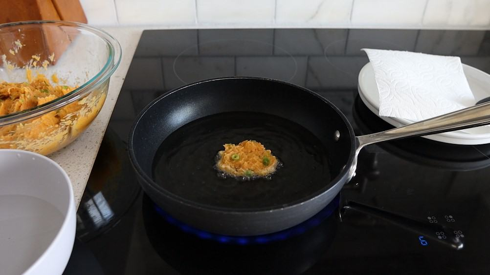 Black skillet with 1 fish patty frying in it.