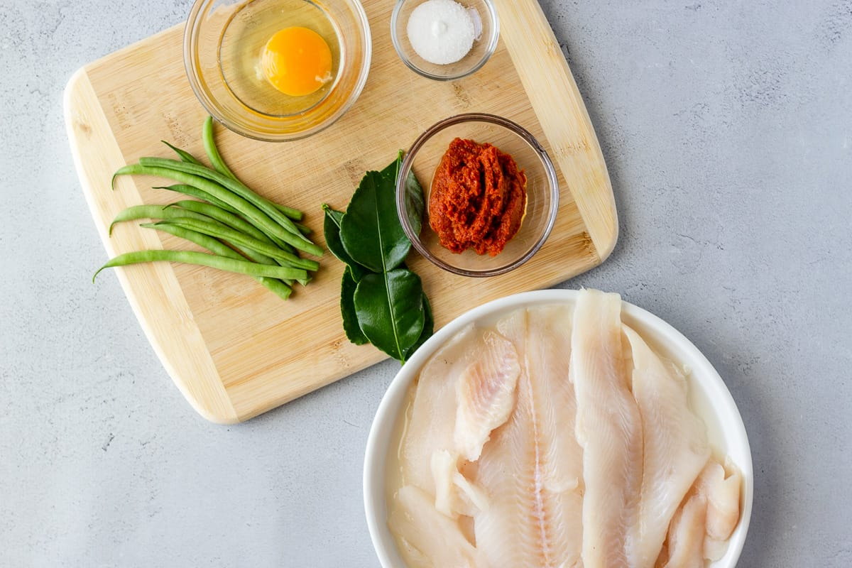 Tilapia on a plate, green beans, lime leaves, egg, curry paste, and sugar on a cutting board.