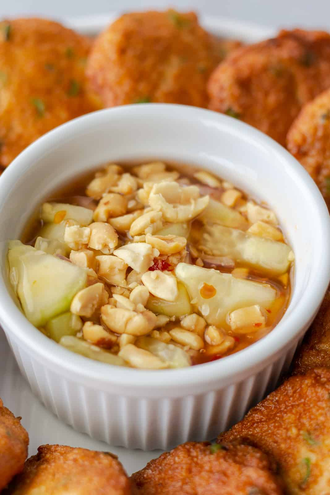 Up close view of sweet chili dipping sauce topped with peanuts.